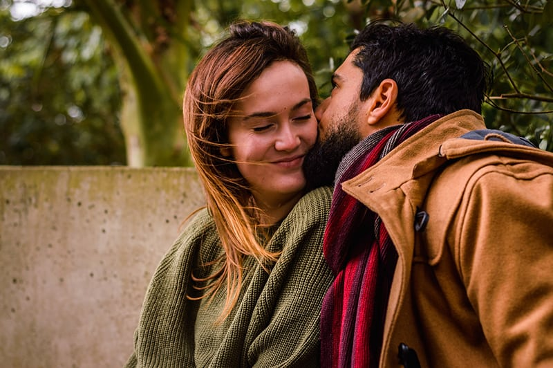 Ein Mann küsst eine Frau auf eine Wange, während er im Freien sitzt