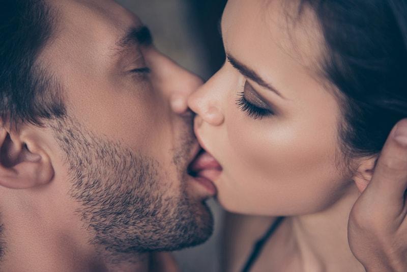 Ein Mann küsst eine Frau mit der Zunge