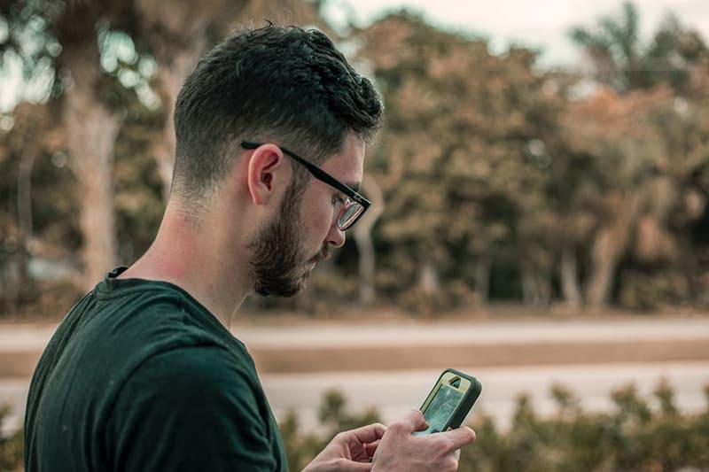 Ein Mann liest eine Nachricht vom Smartphone während des Stehens