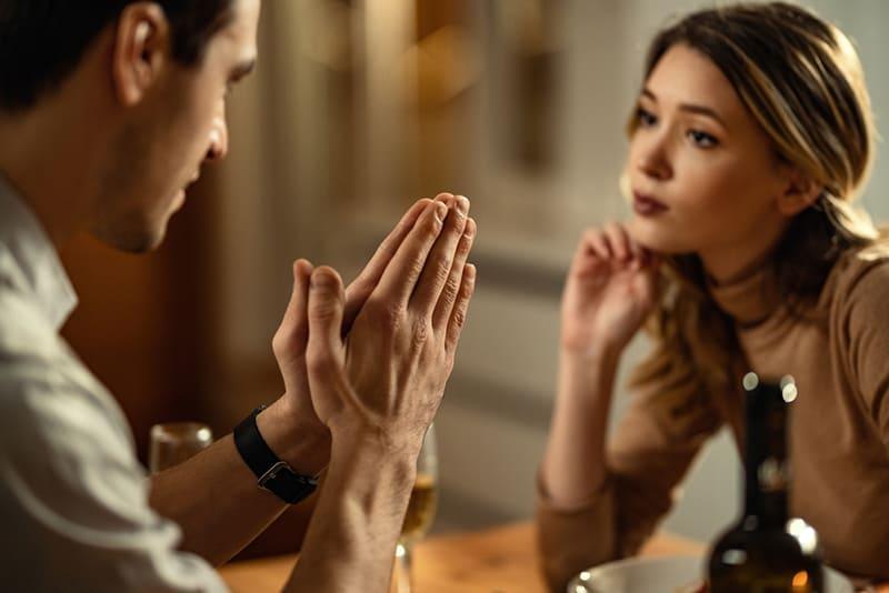 Ein Mann mit gefalteten Händen bat eine Frau um Vergebung