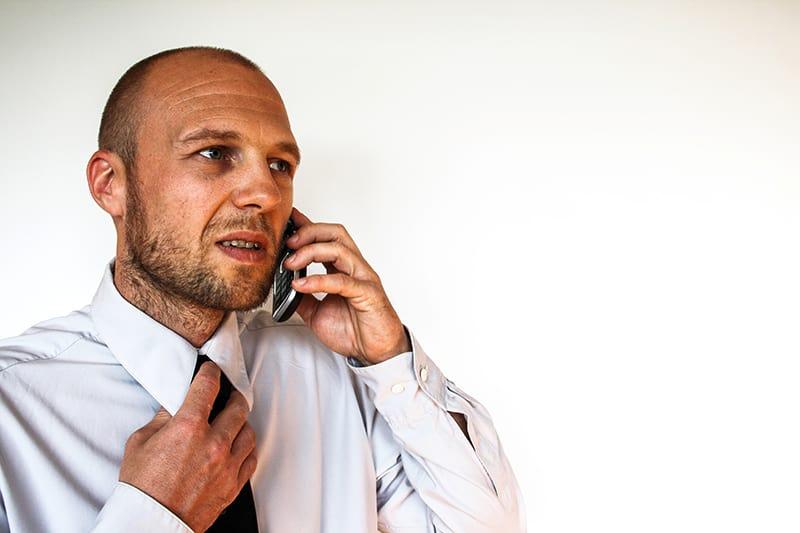Ein Mann ruft seine Freundin an, um ein Date abzusagen, während er eine Krawatte hält