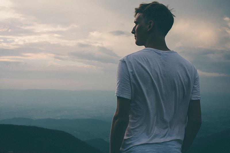 Ein Mann steht auf der Klippe mit Blick auf die Berge und beobachtet den Sonnenuntergang