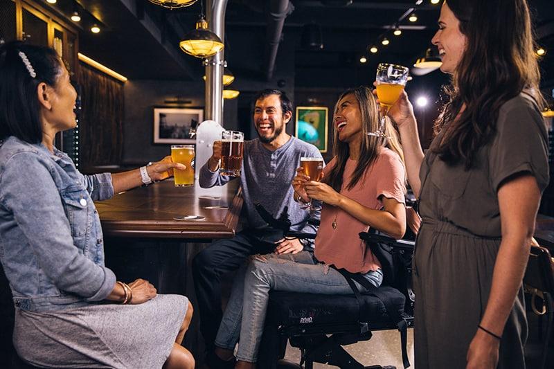 Ein Mann trinkt mit drei Frauen an der Bar