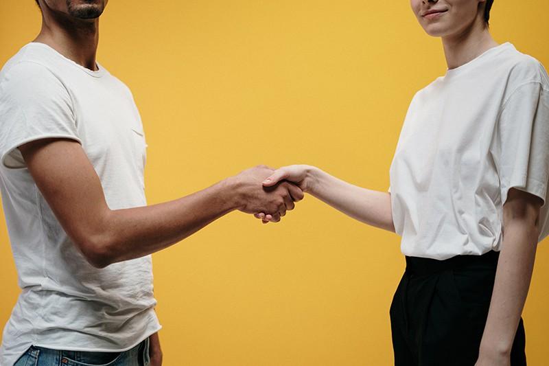 Ein Mann und eine Frau geben sich als Zeichen der Freundschaft die Hand