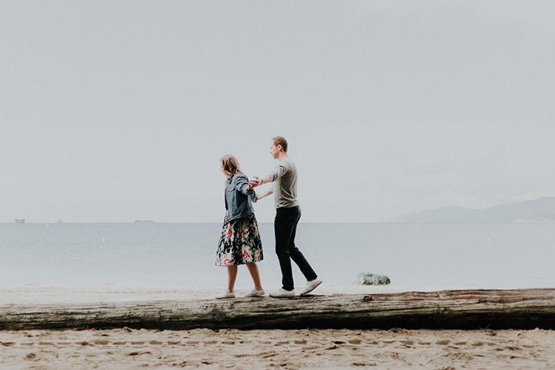 Ein Mann und eine Frau gehen am Strand entlang Während der Tageszeit