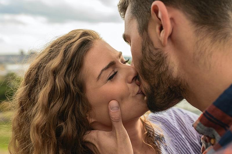 Ein Mann und eine Frau küssen sich auf den Lippen, während sie draußen stehen