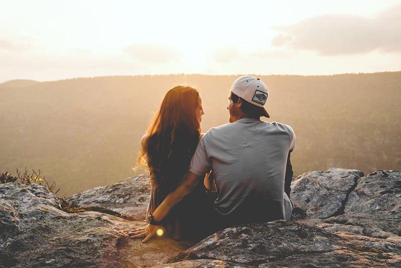 ein Mann und eine Frau sitzen auf dem Felsen während des Sonnenuntergangs