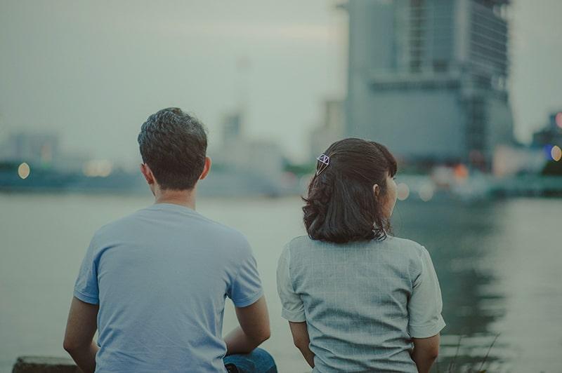 Ein Mann und eine Frau sitzen getrennt auf einer Bank, nachdem sie ihre Beziehung abgebrochen haben
