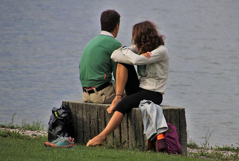 Ein Mann und eine Frau sitzen neben dem Gewässer auf der Betonbank