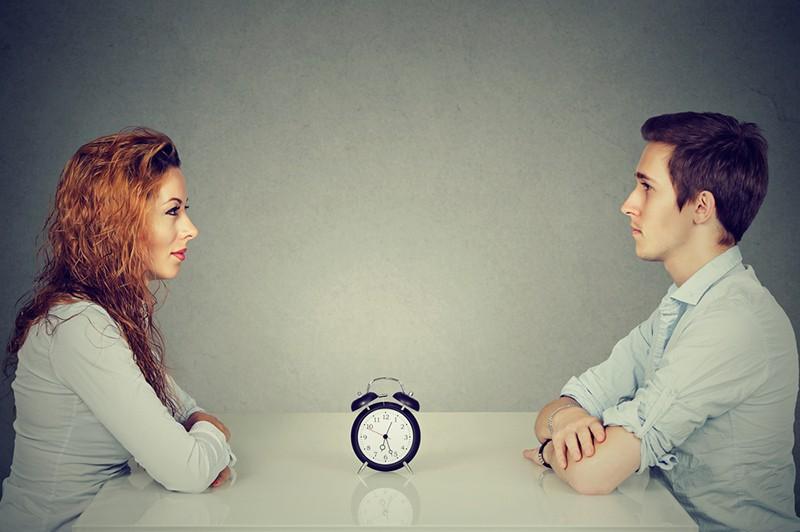 Ein Mann und eine Frau sitzen sich mit einem Wecker dazwischen am Tisch gegenüber während eines Blind Dates