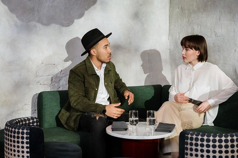 Ein Mann und eine Frau sprechen miteinander, während sie auf dem Sofa sitzen