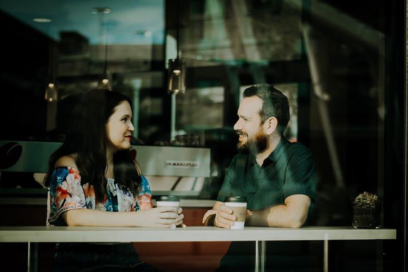 Ein Mann und eine Frau trinken Kaffee in einem Café, während sie reden
