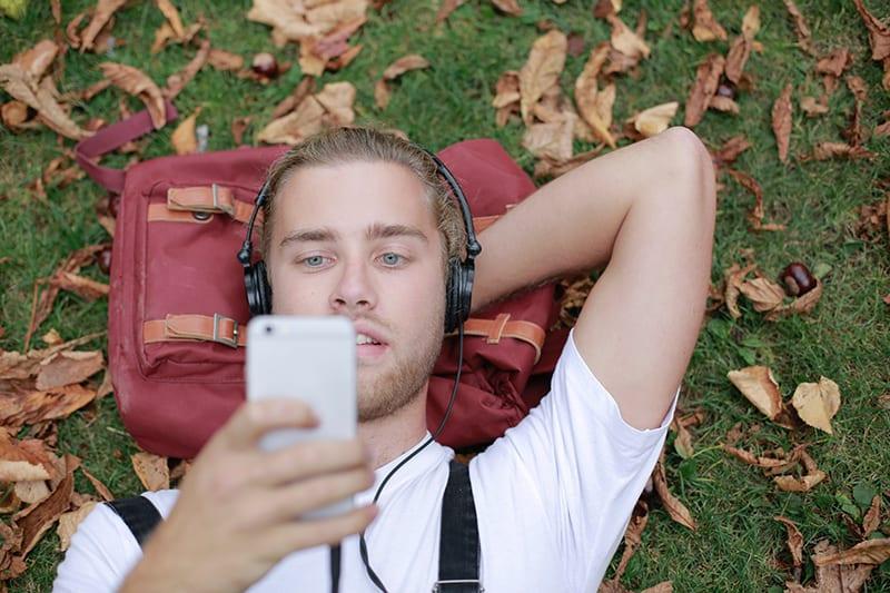 Ein Mann wandert beim Lesen einer SMS vom Smartphone
