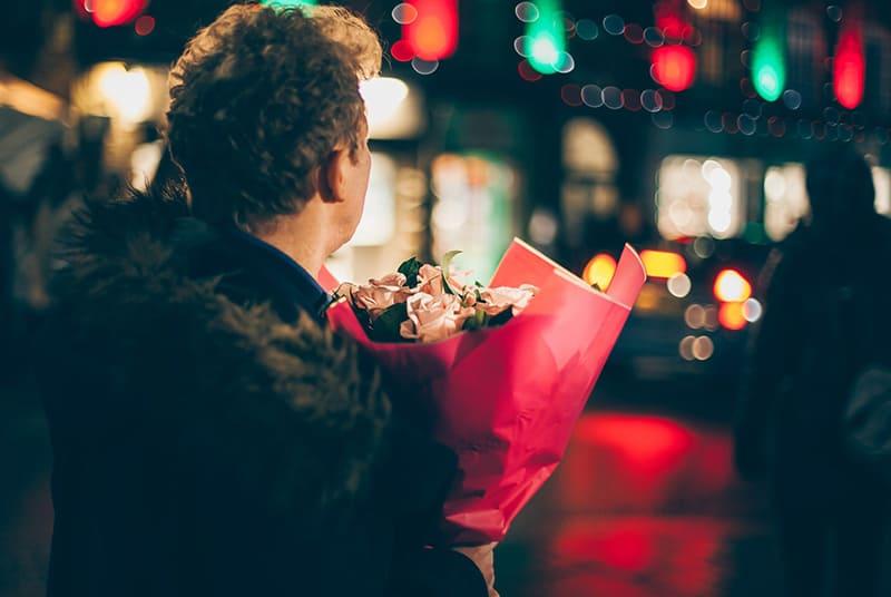 Ein Mann wartet auf seine Freundin und hält einen Blumenstrauß