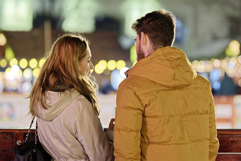 Ein Paar in Jacken unterhält sich draußen