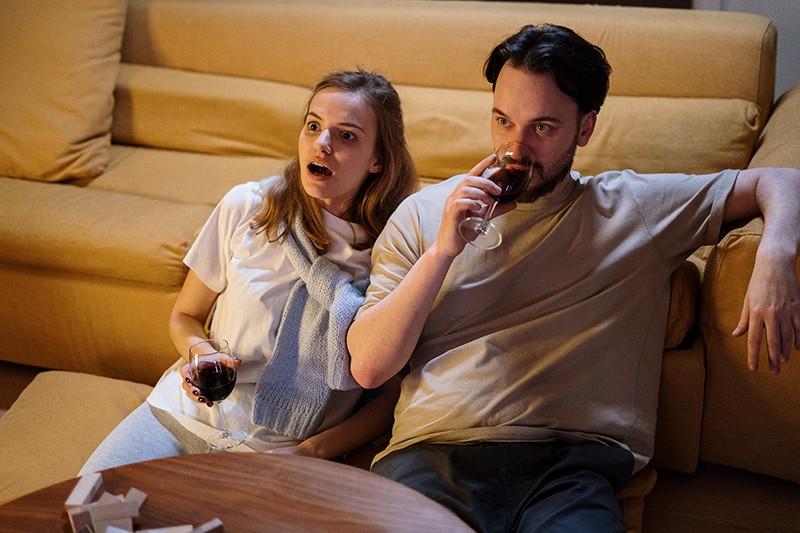 Ein Paar trinkt Wein, während es zu Hause einen Film sieht