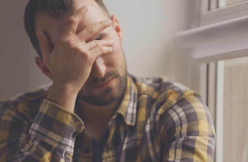 Ein depressiver Mann sitzt am Fenster