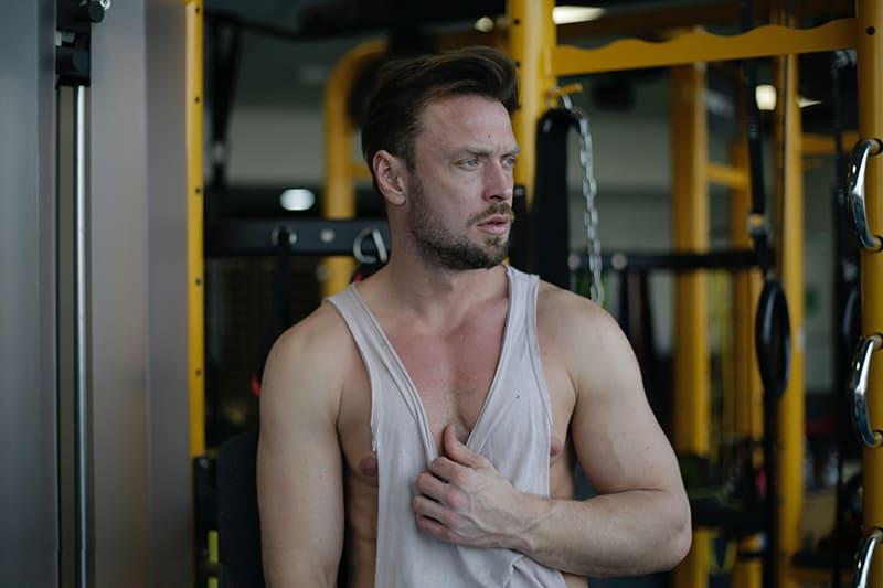 Ein ernster Mann, der im Fitnessstudio steht und zur Seite schaut