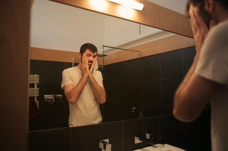 Ein nervöser Mann stand vor dem Spiegel und berührte das Gesicht
