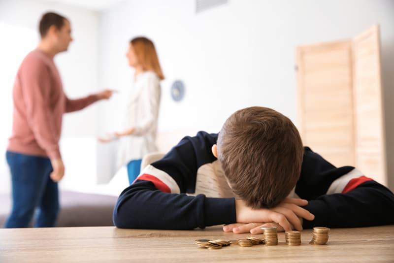 Ein trauriger kleiner Junge, der sich mit Münzen und Eltern, die sich hinter ihm streiten, auf den Tisch lehnt
