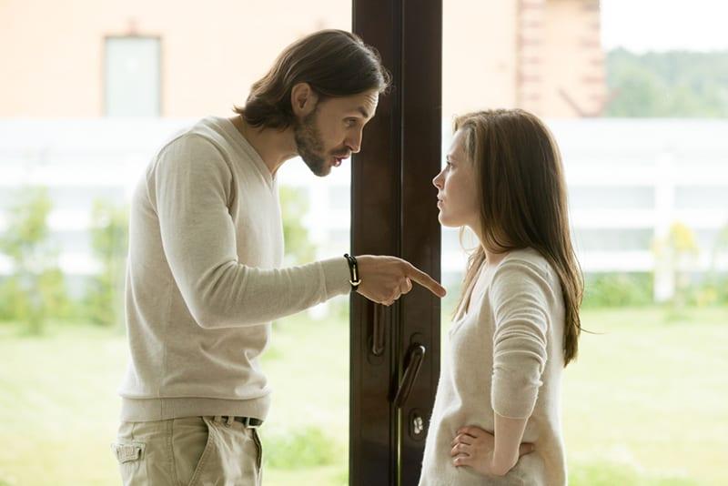 Ein verrückter Mann zeigte mit dem Finger auf eine Frau, die von ihm im Haus hereinkam
