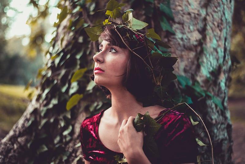 Eine Frau mit einem Kranz im Haar steht neben einem Baum und wartet auf jemanden