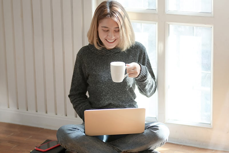 Eine Frau plaudert auf einem Laptop, während sie auf dem Boden sitzt und eine Tasse hält