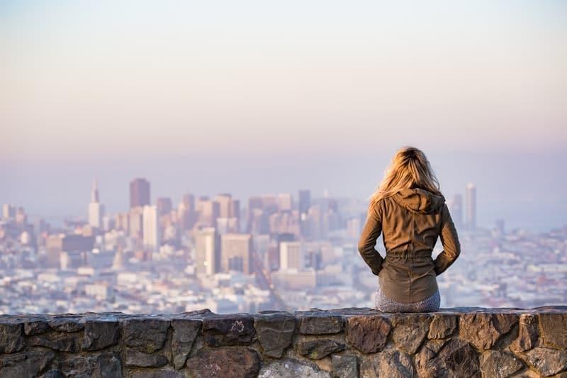 Eine Frau sitzt auf einer Steinmauer