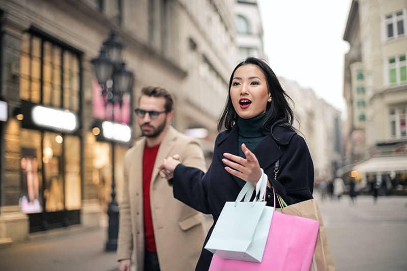 Eine Frau zieht einen verärgerten Mann am Arm auf der Straße