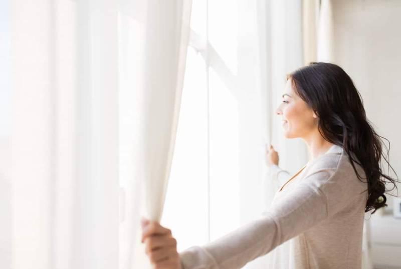 Eine lächelnde Frau schaut aus dem Fenster