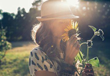 hübsche Dame schnüffelt Blumen