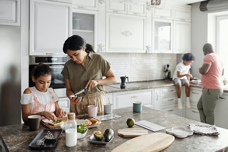 Eltern bereiten mit ihren Kindern Essen in der Küche zu
