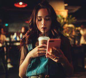 Eine Frau überprüft ihr Telefon, während sie Kaffee trinkt