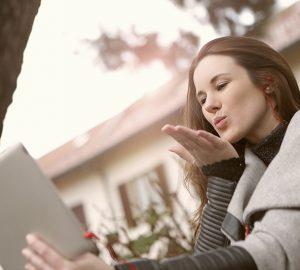 eine Frau, die einen Videoanruf hat, der einen Kuss sendet