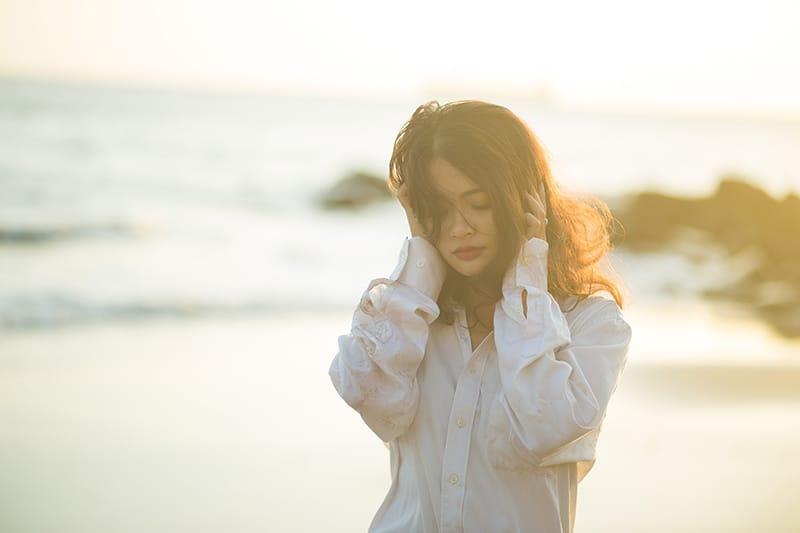 Frau berührt ihren Kopf an der Küste