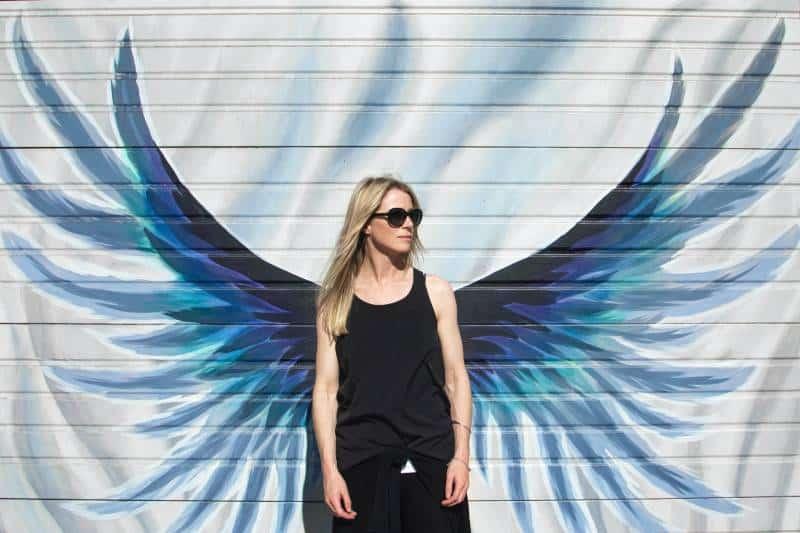 Frau, die Foto nahe Flügel gemalte Wand nimmt