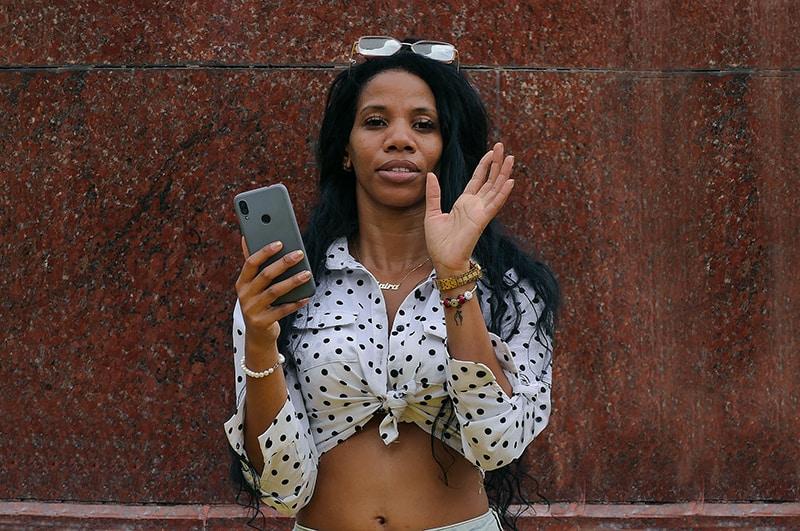 Frau hebt ihre Handfläche, nachdem sie im Stehen eine Telefonnummer blockiert hat