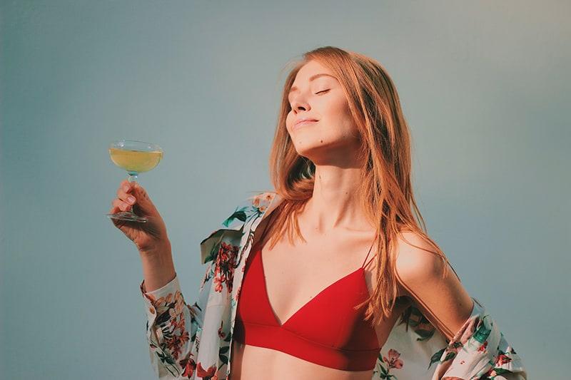 Frau im roten Bikinioberteil, der Getränk hält