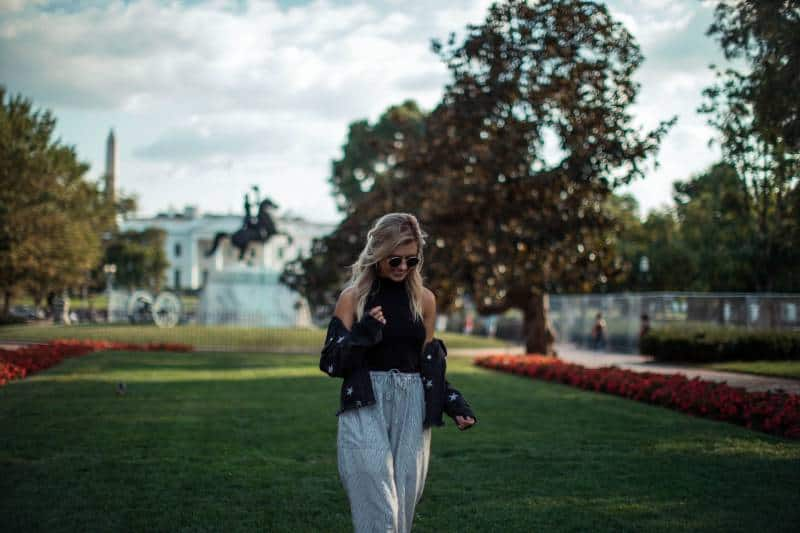 Frau in der schwarzen Spitze, die während des Tages auf grünem Gras steht