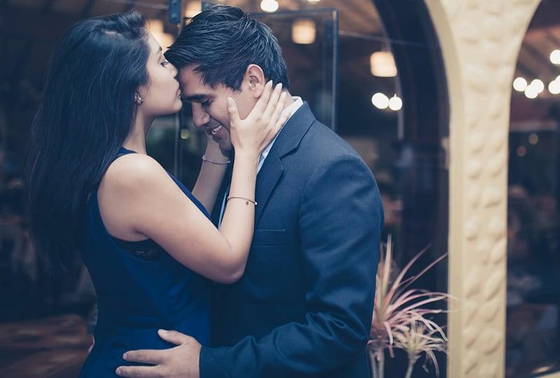 Frau küsst die Stirn des Mannes während des Stehens