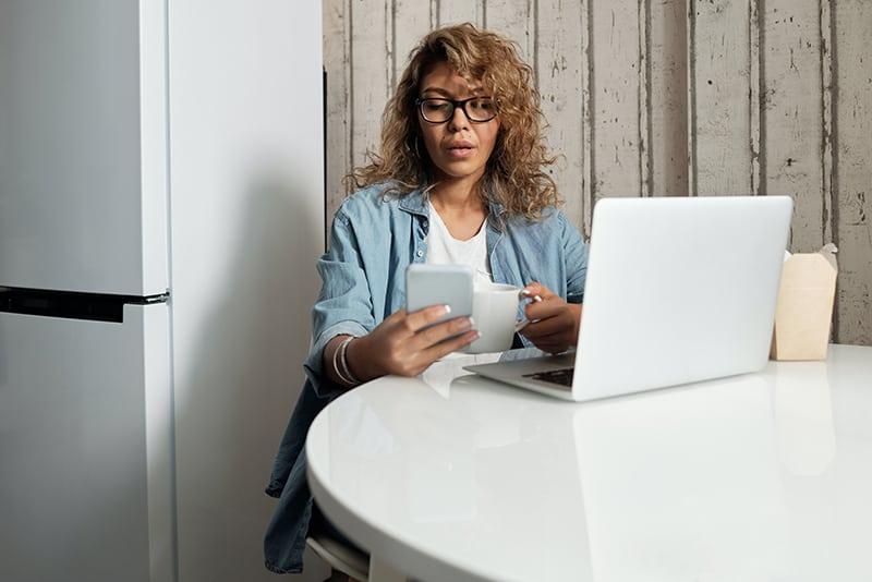 Frau liest eine Nachricht von einem Smartphone mit Zweifel während auf dem Stuhl sitzen