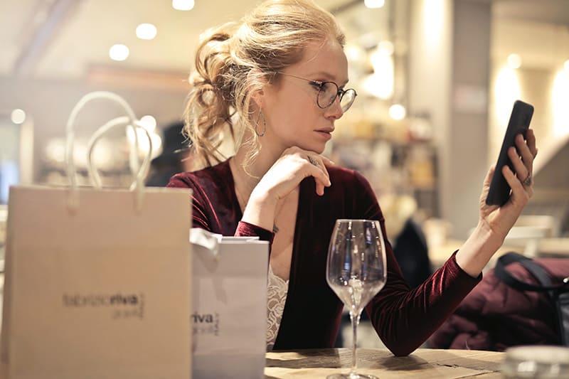 Frau mit ihrem Smartphone beim sitzen am tisch