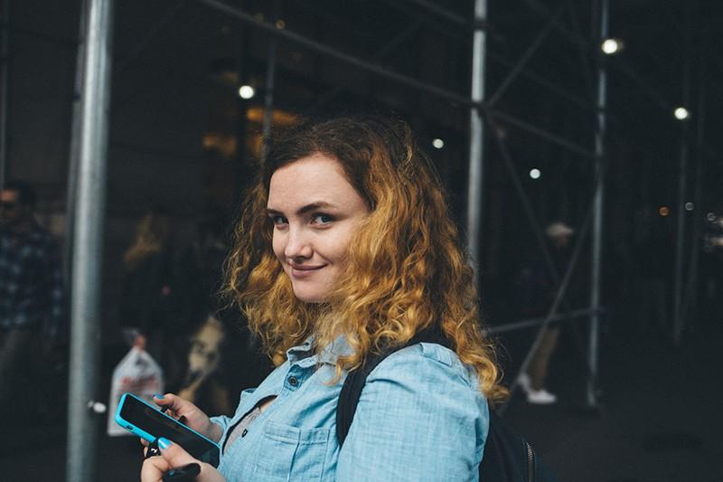 Frau mit lockigem Haar hält Smartphone