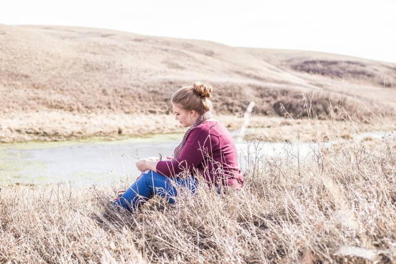 Frau sitzt auf Gras neben Betonstraße am Tag