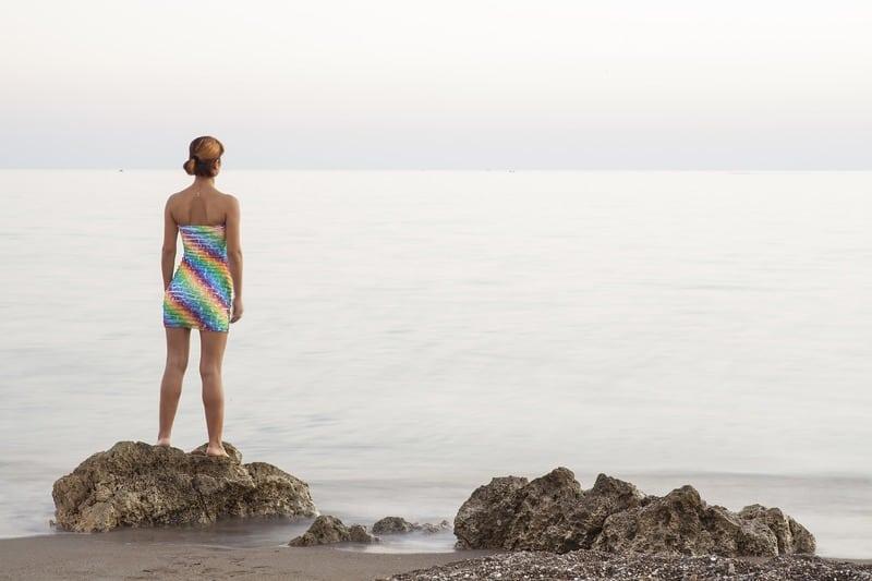 Frau steht auf Stein und schaut auf das Meer