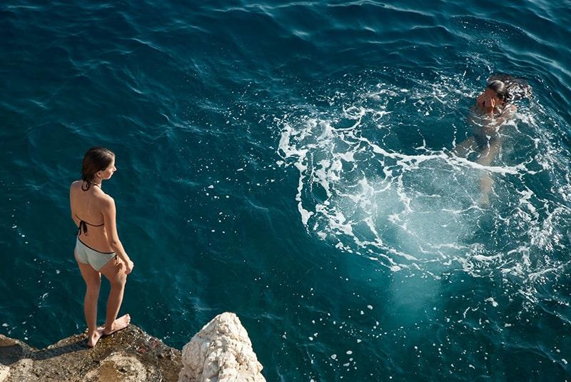 eine Frau, die auf der Klippe steht und ins Meer springen will