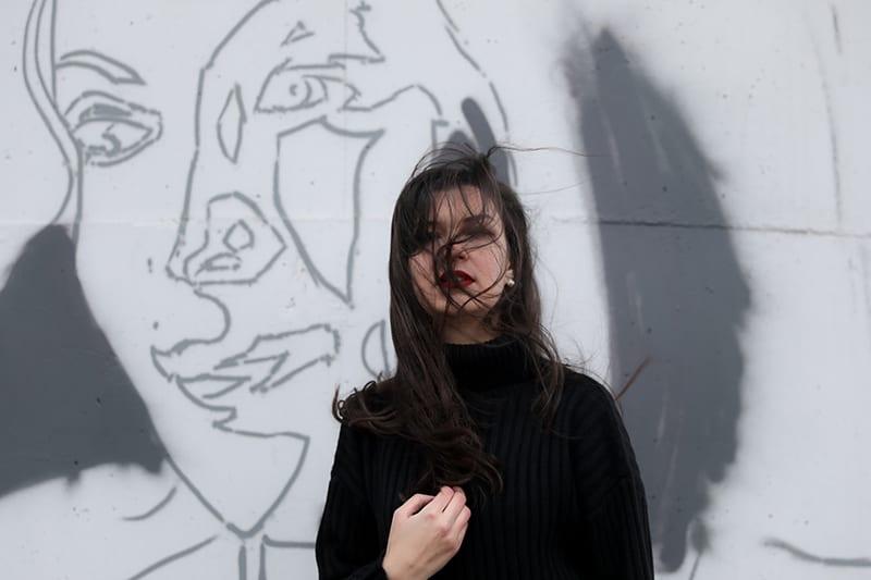 Frau, die schwarzen Pullover trägt, der nahe weißer Wand steht