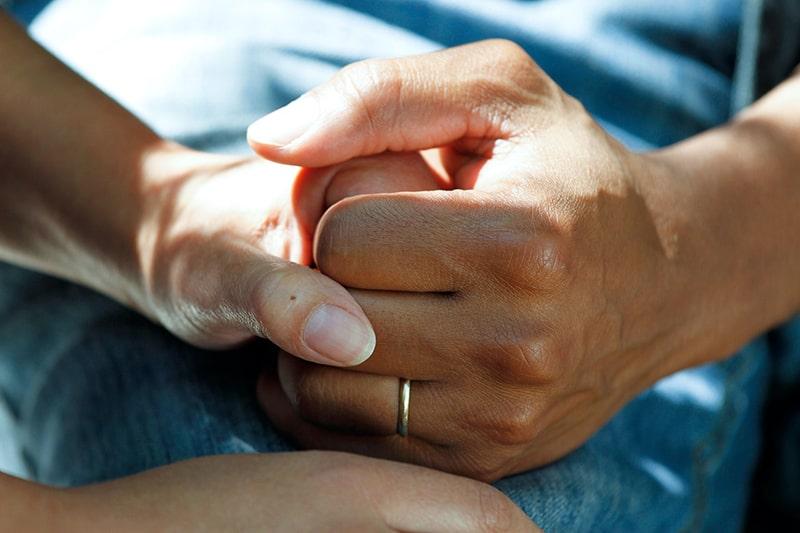 Frau tröstet Mann, während er seine Hand drückt
