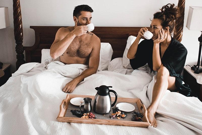 Frau und Mann sitzen auf dem Bett beim Kaffeetrinken