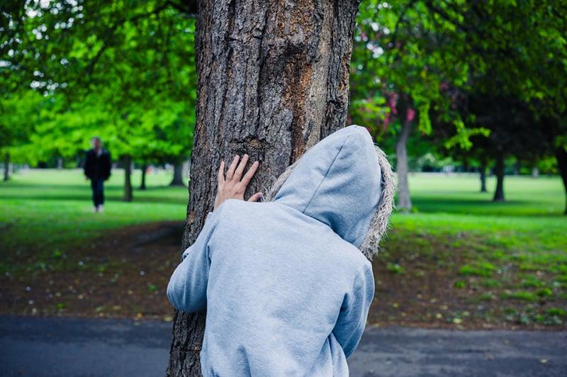 Frau versteckt sich vor Freunden hinter dem Baum